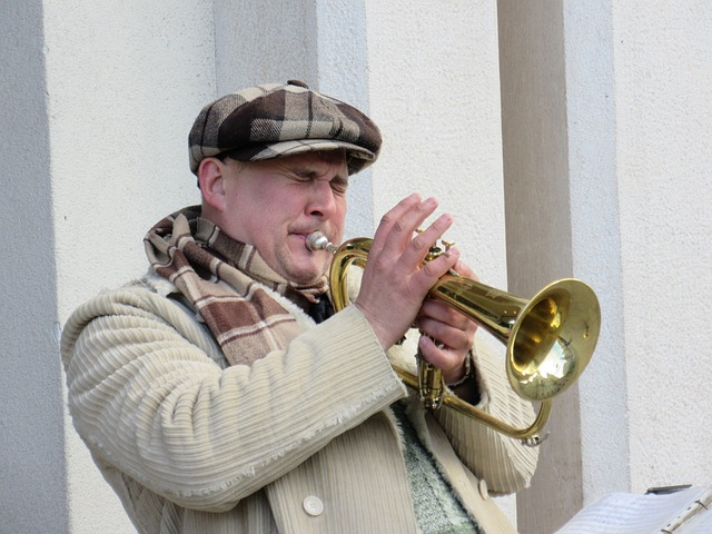 a man playing trumpet with a lot of tension in his body